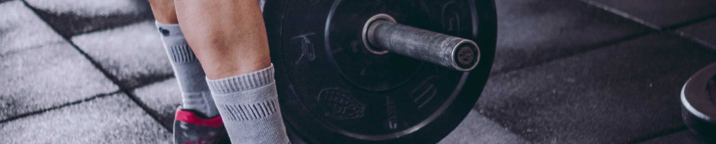 man-picks-up-black-and-grey-barbell-1092874